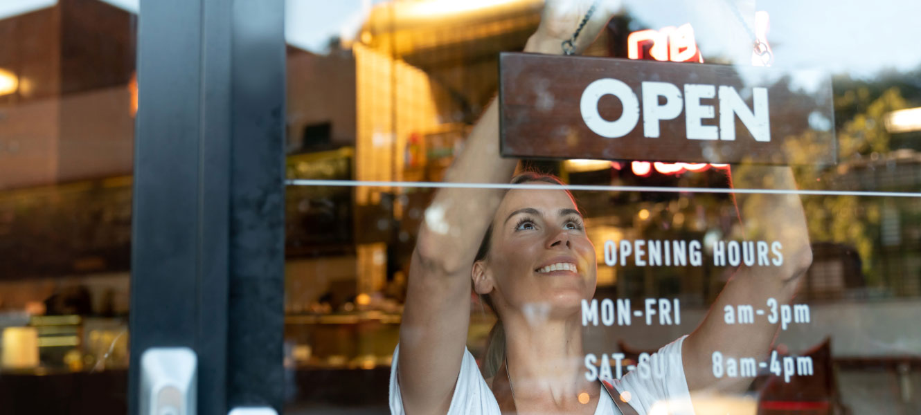 small business owner hanging up open sign